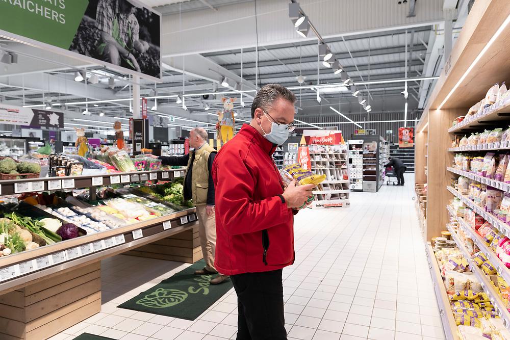 L'Intermarché de La Loupe, le 18 mars 2020<br /> Un client avec un masque sur le visage faiot ses courses au supermarché.