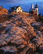 First light of sunrise illuminating wave-sculped rocks leading to the Pemaquid Point Lighthouse, built in 1827, Pemaquid Point, Maine.