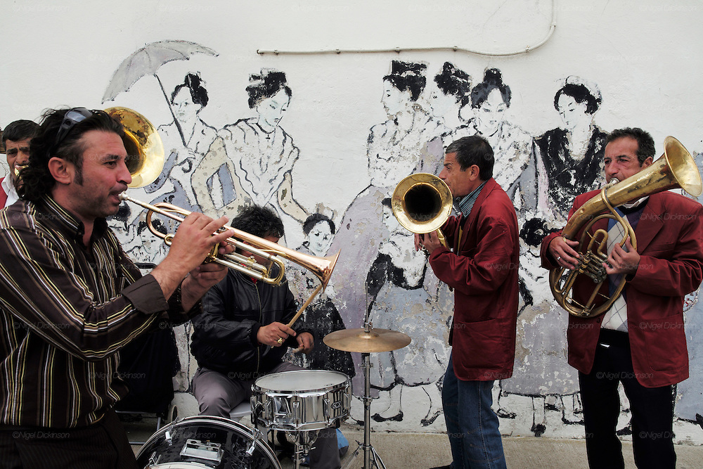 """A Balkan gypsy brass band play inside Saintes Maries de la Mer, with a mural painting of traditional provencal dress in the background<br /><br />A """"Le Pelerinage des Gitans""""; the French gypsy pilgrimage of Saintes Maries de la Mer, Camargue, France<br /><br />Sainte Sara is an uncannonized saint, who legend says looked after the Christian Saints Marie Jacobe and Marie Salome, cousins of Mary Magdalene, who arrived, it is said, on the shores of the Camargue in a rudderless boat. Saint Sara is the patron saint of gypsies who come from far and wide to see her. There are even paintings of Sara as 'Kali' the black saint in Eastern Europe. Sara may have been the priestess of 'Ra' the sun-god or even servant girl to the Christian saints. No-one really knows.<br /><br />For a few weeks of the year, Roma, Gitan and Manouche gypsies come from all over Europe in May, camping in caravans around Saintes Maries de la Mer. It is a festive time where they play music, dance, party and christen their children. They all go to see Saint Sara in the crypt, kissing or touching her forehead. Many put robes on her shoulders, making her fat for the procession. In the main Gypsy procession of the 24th May, Saint Sara is allowed to leave her crypt, beneath the church, and is carried from the church to the shores of the mediterranean and back again. One day a year she is free from her prison. Hundred's of years ago the Gypsies used not even to be allowed into the church, only into the crypt like Sara...<br /><br />Roma gypsies still suffer oppressive prejudice and racism and are one of the ethnic groups the most persecuted and marginalised across Europe. The festival is one of the times where they celebrate with people of all races, their faith and traditions"""