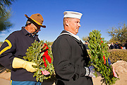 09 DECEMBER 2011 - PHOENIX, AZ:  MIKE CORE, (right) a US Navy reservist, and JOHN ROGERS, a Buffalo Soldier reenactor, carry Christmas wreaths during a wreath laying ceremony in Phoenix. Several hundred volunteers and veterans gathered at the National Memorial Cemetery of Arizona in Phoenix Saturday to lay Christmas wreaths on headstones, a tradition started by Wreaths Across America. Wreaths Across America is a nonprofit organization founded to continue and expand the annual wreath laying ceremony at Arlington National Cemetery begun by Maine businessman, Morrill Worcester, in 1992.  PHOTO BY JACK KURTZ