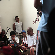 THE PHILIPPINES (Boracay). 2009. Owners wait with their roosters before being prepared for the fight as spectators watch at the cockfighting held at the Boracay Cockpit,  Boracay Island. Photo Tim Clayton <br /> <br /> Cockfighting, or Sabong as it is know in the Philippines is big business, a multi billion dollar industry, overshadowing Basketball as the number one sport in the country. It is estimated over 5 million Roosters will fight in the smalltime pits and full-blown arenas in a calendar year. TV stations are devoted to the sport where fights can be seen every night of the week while The Philippine economy benefits by more than $1 billion a year from breeding farms employment, selling feed and drugs and of course betting on the fights...As one of the worlds oldest spectator sports dating back 6000 years in Persia (now Iran) and first mentioned in fourth century Greek Texts. It is still practiced in many countries today, particularly in south and Central America and parts of Asia. Cockfighting is now illegal in the USA after Louisiana becoming the final state to outlaw cockfighting in August this year. This has led to an influx of American breeders into the Philippines with these breeders supplying most of the best fighting cocks, with prices for quality blood lines selling from PHP 8000 pesos (US $160) to as high as PHP 120,000 Pesos (US $2400)..