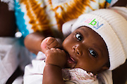 Akua Nshera, 4 months old, sits on her mother's lap at the Osu Maternity Home in Accra, Ghana on Tuesday June 16, 2009.