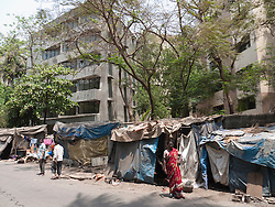 Shanty houses on roadside with flats in background, Mumbai
