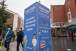 © Licensed to London News Pictures. 12/10/2020. LONDON, UK. People wearing facemasks pass a prominent social distancing sign in Harrow town centre.  It is reported that five London boroughs had more than 100 new COVID-19 cases per 100,000 population in the week to October 8 — Richmond, Hackney, Ealing, Redbridge and Harrow.  As the UK experiences a rise in the number COVID-19 cases nationwide, Boris Johnson, Prime Minister is announcing in the House of Commons a new three-tier local lockdown system to tackle the spread of the virus.  Photo credit: Stephen Chung/LNP