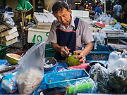 30 DECEMBER 2015 - BANGKOK, THAILAND:  A vendor scoops the meat out of a coconut in Bang Chak Market. The market is supposed to close permanently on Dec 31, 2015. The Bang Chak Market serves the community around Sois 91-97 on Sukhumvit Road in the Bangkok suburbs. About half of the market has been torn down. Bangkok city authorities put up notices in late November that the market would be closed by January 1, 2016 and redevelopment would start shortly after that. Market vendors said condominiums are being built on the land.           PHOTO BY JACK KURTZ