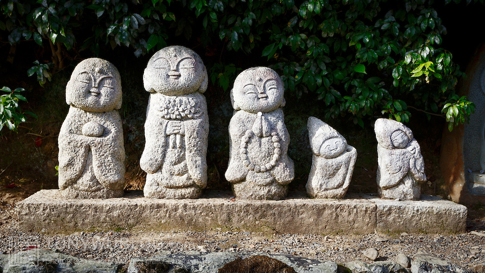 Five cute Buddhist figures along the road in front of Tenryu-ji in Kyoto.