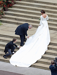 The Duke of York helps to adjust the train on Princess Eugenie's wedding dress as she arrives for her wedding to Jack Brooksbank at St George's Chapel in Windsor Castle.