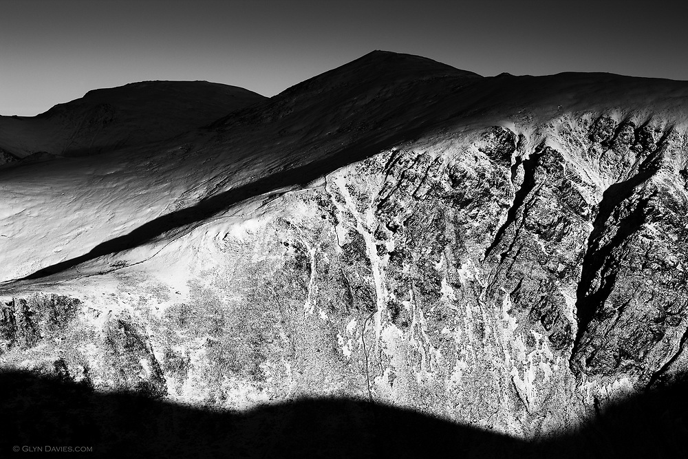 An isolated large cloud passed over a cloudless blue sky and darkened all the hill tops of the Carneddau in the distance, but intense sunlight continued to blast the 1000ft cliffs just ahead of me, beautiful and natural tonality