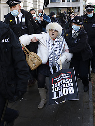 © Licensed to London News Pictures. 06/01/2021. London, UK. A demonstrator is removed by police outside Westminster Magistrates court in central London as a bail hearing for Wikileaks founder Julian Assange takes place. Bail had been denied. The bail hearing is being heard after a judge at a recent heaing blocked his extradition to the USA. Photo credit: Peter Macdiarmid/LNP