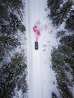 Aerial view of a man lighting a pink smoke grenade on a snowy road in the forest in Estonia.