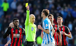 Referee Anthony Taylor shows Huddersfield Town's Jon Gorenc Stankovic the yellow card during the Premier League match at the John Smith's Stadium, Huddersfield.