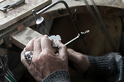 Senior goldsmith shaping crystal with hand saw in workshop, Bavaria, Germany