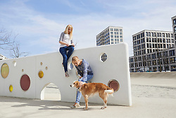 Teenage girl using a digital tablet and her friend stroking her dog in playground, Munich, Bavaria, Germany