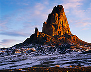 Warm light of winter sunrise stricking the volcanic neck of 7,100 foot Agathla Peak, Navajo Reservation, Arizona.