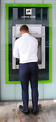 People use a cash machine by the Lloyds Banking Group head offices in London, as the banking giant is cutting 1,230 jobs in its group operations, retail, marketing and finance divisions as part of previously announced three-year strategy.