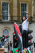 """London, United Kingdom, May 11, 2021: A Pro-Palestinian demonstrator takes a selfie as he climbed on a traffic light outside Downing Street to protest against Israeli air raids on Gaza Strip. Demonstrators chanted """"Free-Free Palestine!"""" demanding the commitment of Great Britain to end their support for Israel. (Photo by Vudi Xhymshiti/VXP)"""