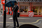 A businessman struggles to put up an umbrella in front of construction site stripes.