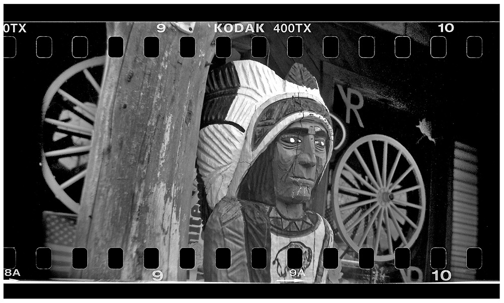 A statue of a Native American is seen at the entrance of a souvenir shop in Crawford, Texas, December 13, 2008. Bush moved to the small Texas town, population 705, in 1999 during his run for the presidency in 2000. The effect of the image was achieved by shooting 35mm black and white film in a medium format camera thereby exposing the entire negative including the sprocket holes of the film. REUTERS/Jim Young