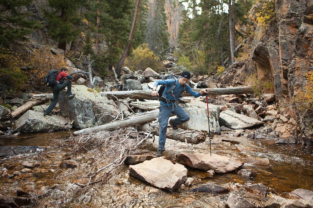 David Coffey (right) and Obadiah Reid carefully hike down Big Thompson River, Rocky Mountain National Park, Colorado.