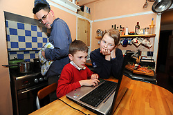 Brother & sister using laptop in kitchen whilst father cooks and looks worried MR