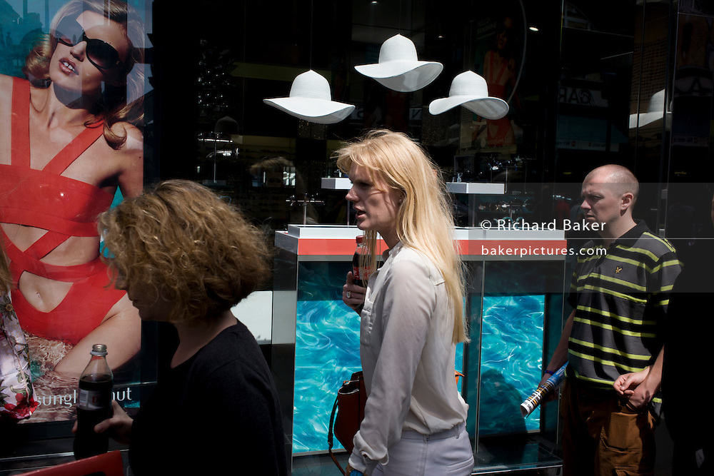Consumers walk past a sunglasses shop featuring three hats suspended from the store window ceiling.