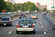 State Police car travelling among volume of traffic on freeway, outskirts of Washington DC, USA