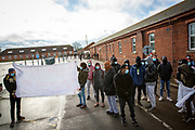 Asylum seekers currently held inside Napier Barracks staged a peaceful protest inside the entrance to the barracks with banners and signs to demonstrate about the poor conditions they are subjected to inside the holding centre on the 12th of January 2021, Folkestone Kent. Over 400 asylum seekers are being kept at Napier Barracks in unsuitable, cold accommodation, they are experiencing mental health issues as well as being vulnerable to health conditions including COVID-19.  (photo by Andy Aitchison)