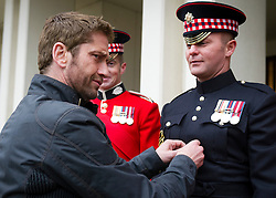 © Licensed to London News Pictures. 04/04/2013. London, UK Hollywood actor Gerard Butler jokes with Sergeant (Sgt) John Norwood of F Company the Scots Guards.  Butler met the soldiers at Wellington Barracks in Central London ahead of a special preview screening of Hollywood movie Olympus Has Fallen, released 17th April 2013. ..The actors spent time talking to the soldiers prior to the troops watching a special preview of the film in the barracks. Photo credit : Alison Baskerville/LNP