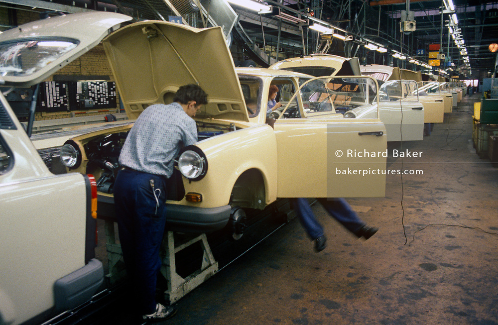 """Six months after the fall of the Berlin Wall, the last Trabant cars come off the factory production line, on 1st June 1990, in Zwickau, eastern Germany (former DDR). The DDR-produced Trabant suffered poor performance, but its smoky two-stroke engine regarded with affection as a symbol of the more positive sides of East Germany. Many East Germans streamed into West Berlin and West Germany in their Trabants after the opening of the Berlin Wall. It was in production without any significant change for nearly 30 years. The name Trabant means """"fellow traveler"""" in German."""
