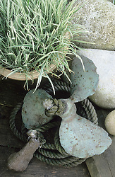 Decorative arrangement of old propeller, rope and stones.