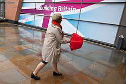 © Licensed to London News Pictures. 02/10/2012. Manchester, UK . A woman with a red umbrella and scarf arrives at the venue . Labour Party Conference Day 3 at Manchester Central . Photo credit : Joel Goodman/LNP