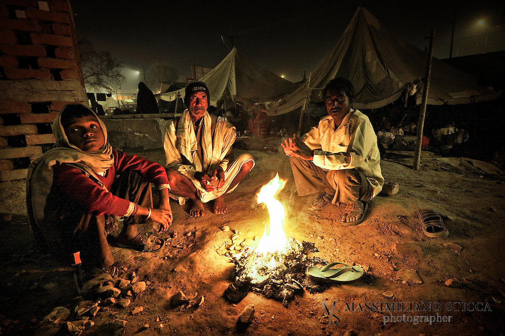 Pilgrims after the Mauni Amavasya day, are warming near the fire.