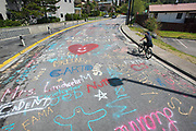 A cyclist  views street art created by the Ketchikan High School 2020 graduating senior class on Wednesday, May 5, 2020 at 5th Avenue and Madison Street in Ketchikan, Alaska. The student artwork featured names of Kayhi teaching staff and faculty.