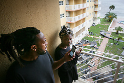 October 7, 2016 - Titusville, Florida, U.S. - WILL VRAGOVIC   |   Times.Brian Farmer, 32, and Ciara Harris, 23, take photos from a balcony overlooking the courtyard in the Bay Towers apartments in Titusville, Fla. on Friday, Oct. 7, 2016. City officials condemned the building after winds from Hurricane Matthew tore large sections of the roof off, and at least 50 people are being displaced. (Credit Image: © Will Vragovic/Tampa Bay Times via ZUMA Wire)