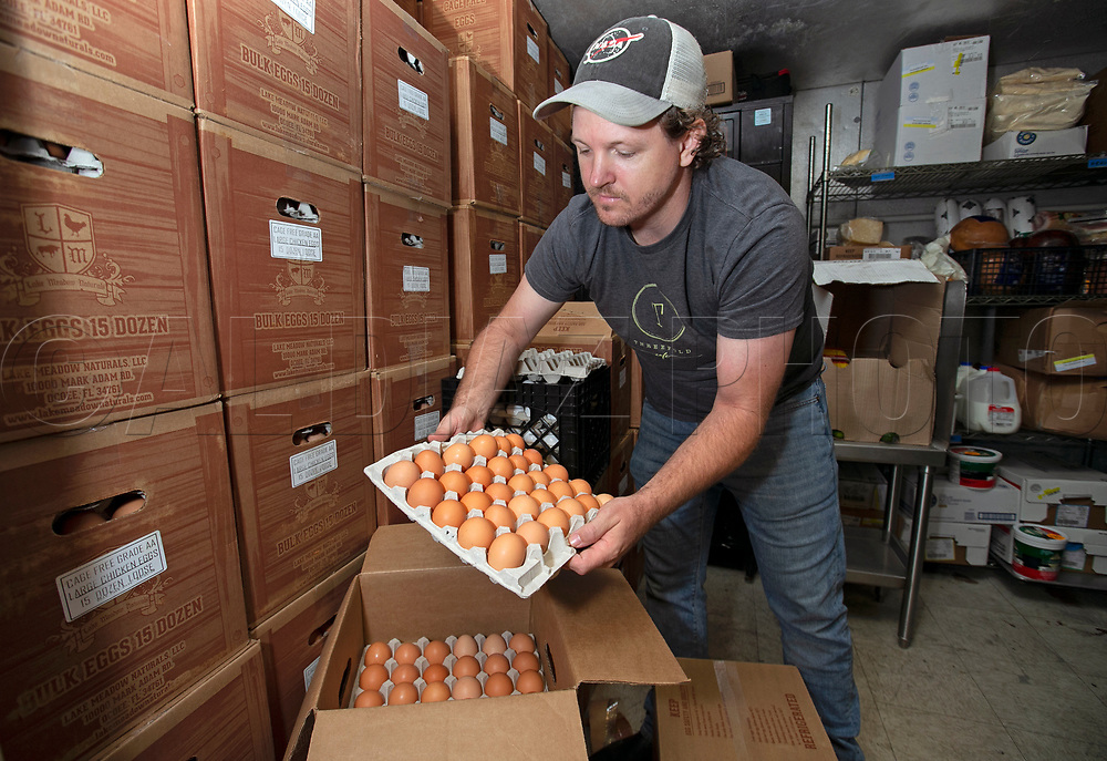 At Three Folds Cafe, owner Nick Sharp with the cases of eggs in cold storage on Wednesday, March 25, 2020. Due to COVID-19 many restaurants have adjusted their hours and offer expanded services for pick up or delivery and several are turning to selling groceries, including eggs, that would be otherwise stuck up the supply chain at farms, dairies and ranches.