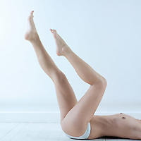 studio shot picture of a young beautiful breast naked  woman lying on a white floor flapping legs