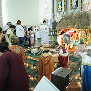 Visitors pay their respects at a Christmas nativity scene while the priest looks on at the Cathedral of San Gervasio (Catedral De San Gervasio) inValladolid in the heart of Mexico's Yucatan Peninsula.