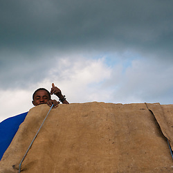 A young worker riding on the back of a truck gives a thumbs up.  This truck could be carrying food aid to the south, equipement for the new roads or on it's way to Kenya.