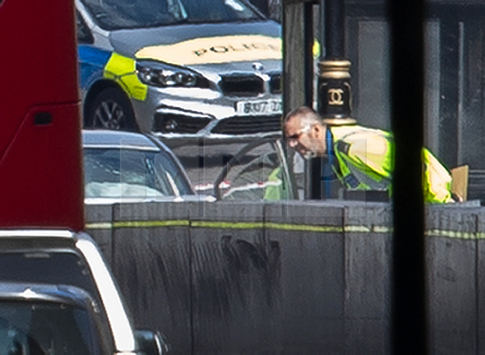 © Licensed to London News Pictures. 14/08/2018. London, UK. A police officer looks into the damaged silver car that crashed into barriers outside Parliament. A number of pedestrians are injured. The driver has been arrested.  Photo credit: Peter Macdiarmid/LNP