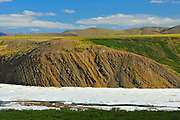 Late winter snow in mid June  on the tundra with the Richardson Mountains on the Dempster Highway north of the Arctic Circle into NWT<br /> Dempster Highway<br /> Northwest Territories<br /> Canada