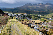 A slate mine track descends towards the town of Blaenau Ffestiniog, on 5th October 2021, in Blaenau Ffestiniog, Gwynedd, Wales. The derelict slate mines around Blaenau Ffestiniog in north Wales were awarded UNESCO World Heritage status in 2021. The industry's heyday was the 1890s when the Welsh slate industry employed approximately 17,000 workers, producing almost 500,000 tonnes of slate a year, around a third of all roofing slate used in the world in the late 19th century. Only 10% of slate was ever of good enough quality and the surrounding mountains now have slate waste and the ruined remains of machinery, workshops and shelters have changed the landscape for square miles.