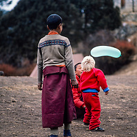 A young trekker plays with young monks at Tengboche Monastery in the Khumbu region of Nepal 1986.