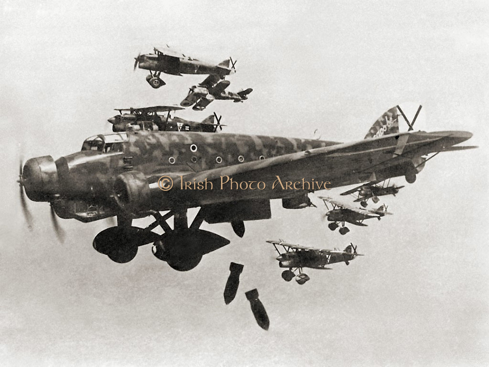 A Savoia-Marchetti SM.81 during a bombing raid. The black crosses distinctives in the tails are Saint Andrew's Cross, the insignia of the Spanish Nationalist Air Force (Franco side). Small planes are FIAT CR.32 of the Italian XVI Gruppo Autonomo Cucaracha. Spanish Civil War
