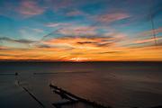 Streaks of light dissect the sky at sunrise over Navy Pier.