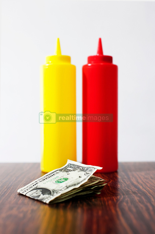 Money on table next to mustard and tomato sauce (Credit Image: © Image Source/Julian Ward/Image Source/ZUMAPRESS.com)