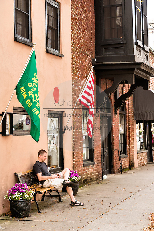 A man rests on a bench along East Bay Street in historic Charleston, SC.