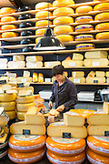 Shelves of cheese wheels and woman cutting cheese wedge at cheese shop 't Kaaswinkeltje in Gouda, Holland, The Netherlands