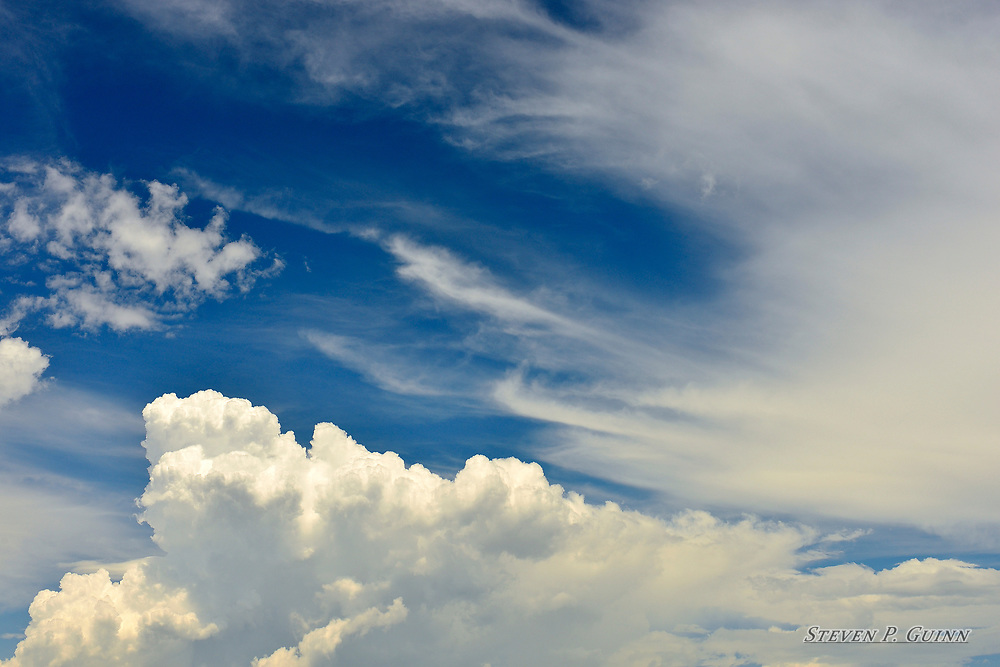 """I captured this image while I was in Rensselaer, Indiana on June 14th, 2017. What caught my eye the most about these cloud formations was the way the cumulus clouds (fluffy), altocumulus clouds (patchy), and cirrus clouds (wispy) are spread through such a wide area. I also used a circular polarizer lens filter to darken the blue sky while keeping the illumination from the the sun on the cumulus clouds. I wanted to darken the sky to accentuate the edges of the cumulus clouds and produce a contrasting background. <br /> <br /> Printed on Hahnemühle German Etching paper. Limited to 100 productions per size.<br /> <br /> Framed prints are available in 18"""" x 12"""", 24"""" x 16"""", 30"""" x 20"""", 36"""" x 24"""", 45"""" x 30"""", and 60"""" x 40"""" sizes."""