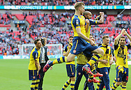 Arsenal's Per Mertesacker and Arsenal's Theo Walcott jump together  during the The FA Cup match between Arsenal and Aston Villa at Wembley Stadium, London, England on 30 May 2015. Photo by Phil Duncan.