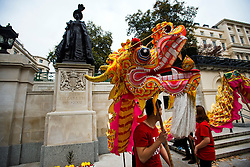 © Licensed to London News Pictures. 20/10/2015. London UK. A Chinese dragon performs in front of a state of the late Queen Mother, Elizabeth, on The Mall in London leading to Buckingham palace as Chinese President Xi Jinping starts day one of a four day State Visit to the United Kingdom. Photo credit: Ben Cawthra/LNP